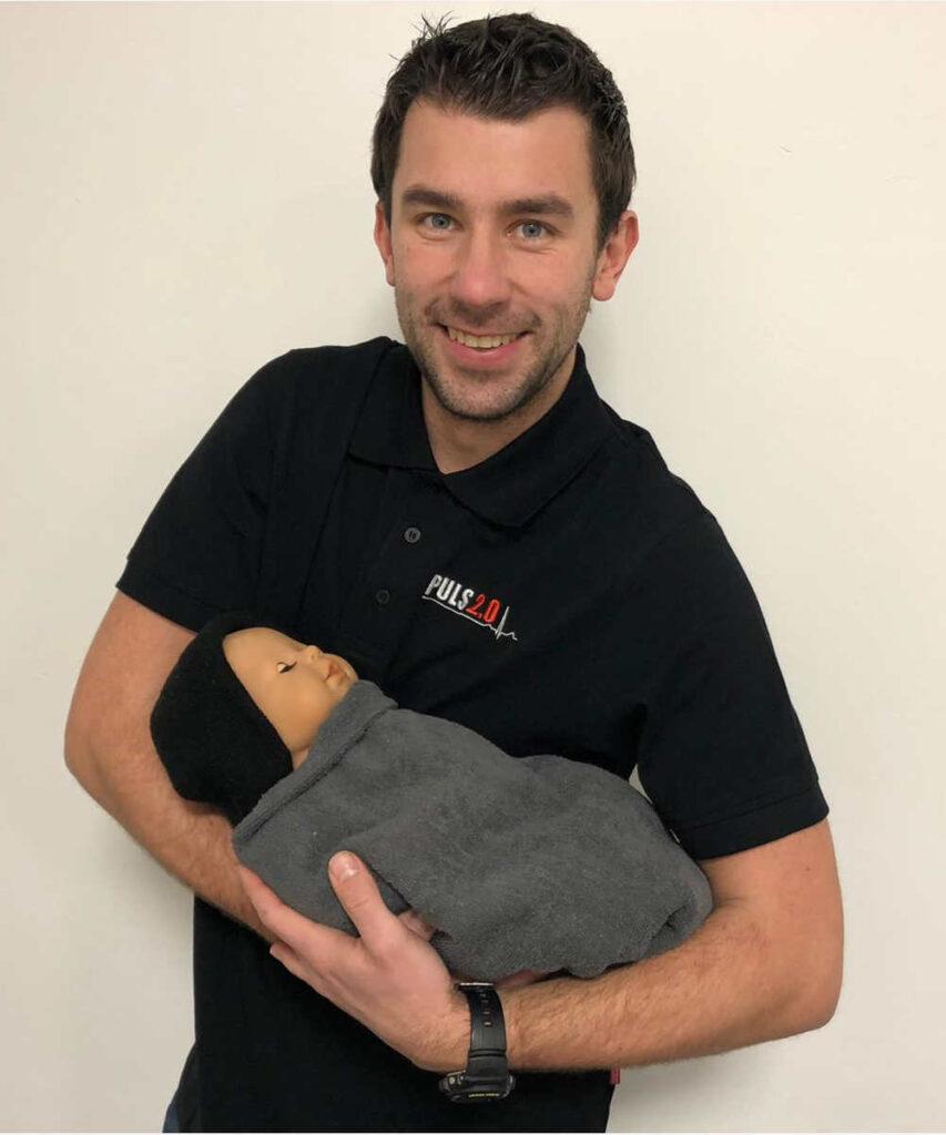 Ausbilder hält Erste Hilfe Baby auf dem Arm